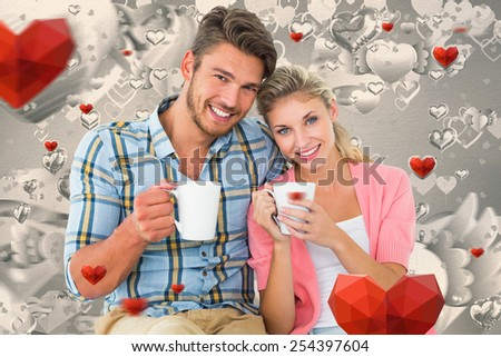 Attractive young couple sitting holding mugs against grey valentines heart pattern - stock photo
