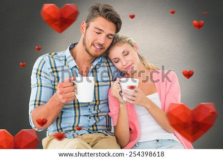 Attractive young couple sitting holding mugs against white background with vignette - stock photo