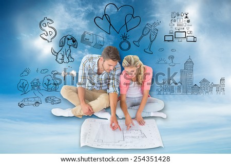 Attractive young couple sitting looking at blueprint against blue sky - stock photo
