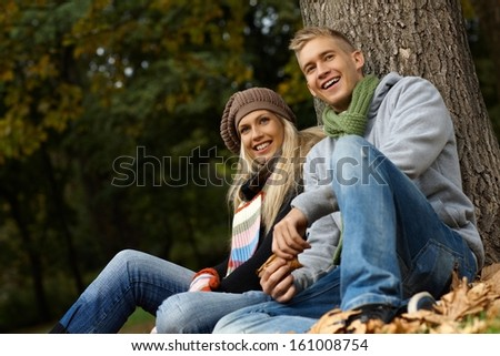 Attractive young couple sitting on ground in autumn park, smiling.