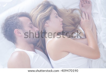 Attractive young couple sleeping calm in bed - stock photo
