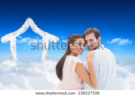 Attractive young couple smiling at camera against bright blue sky over clouds - stock photo