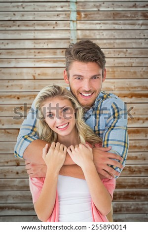 Attractive young couple smiling at camera against wooden background in pale wood - stock photo