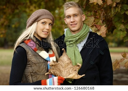 Attractive young couple smiling in autumn park.