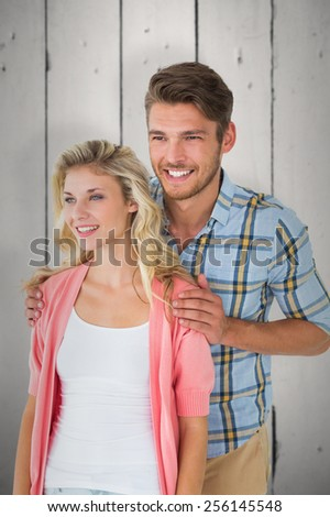 Attractive young couple smiling together against white wood - stock photo