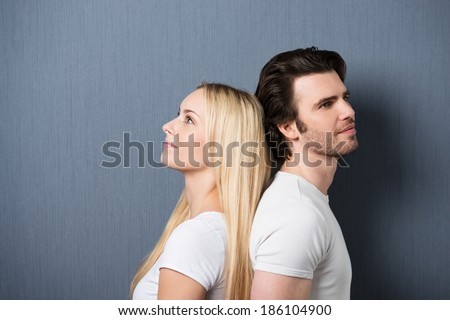 Attractive young couple standing back to back both staring thoughtfully into the distance with quiet smiles, on grey - stock photo