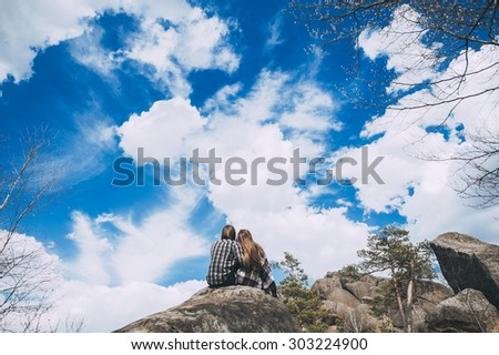 Attractive Young  Couple, standing on rocks, with bright blue sky behind variation