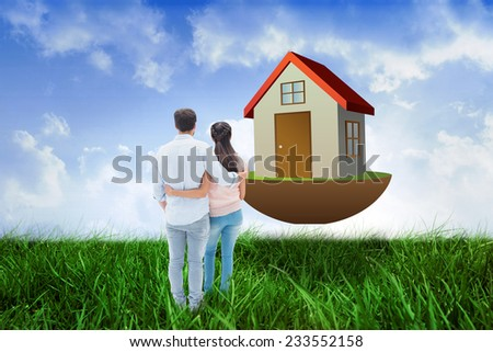 Attractive young couple standing with arms around against field of grass under blue sky - stock photo