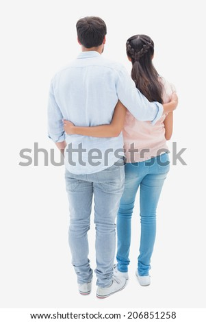 Attractive young couple standing with arms around on white background