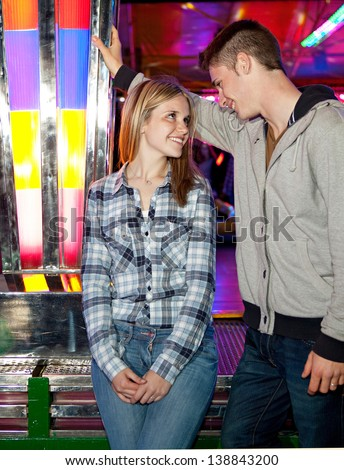 Attractive young couple visiting an amusement park arcade standing by a bouncy cars ride, talking and having fun during an exciting night out.