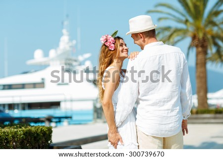 Attractive young couple walking alongside the marina with moored boats on a luxury waterfront in summer sunshine - stock photo