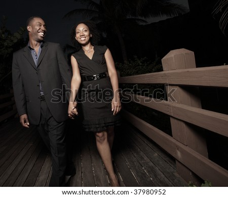 Attractive young couple walking at night - stock photo