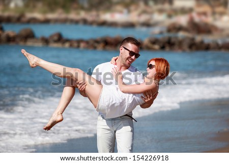 attractive young couple walking on seashore