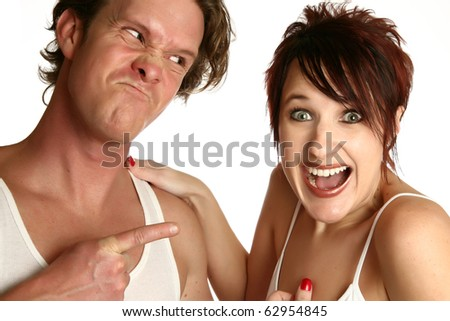 Attractive young couple with different emotions. Man angry woman laughing.  Over white background. - stock photo