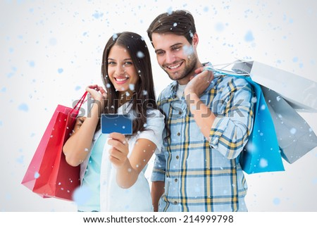 Attractive young couple with shopping bags and credit card against snow falling - stock photo
