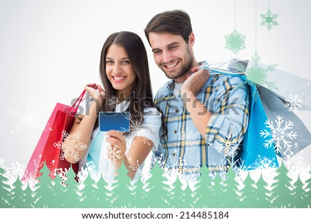 Attractive young couple with shopping bags and credit card against snowflakes and fir trees in green - stock photo