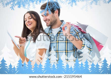 Attractive young couple with shopping bags and tablet pc against frost and fir trees - stock photo