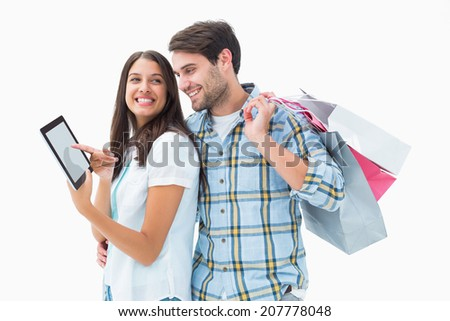 Attractive young couple with shopping bags and tablet pc on white background - stock photo