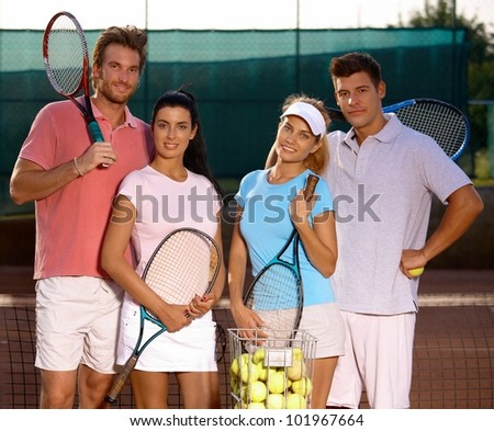 Attractive young couples standing on tennis court, smiling, looking at camera. - stock photo