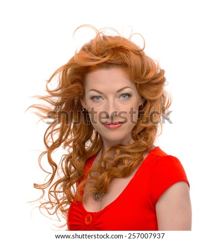 Attractive young curly redhead woman in red dress on isolated background
