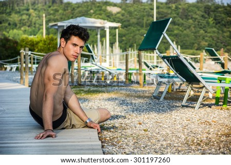 Attractive Young Dark Haired Man Lying on Stomach on Sun Deck with Lounge Chairs, Outdoors on Sunny Day with Forest in Background - stock photo