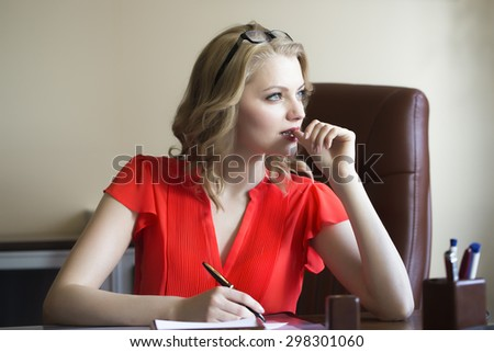 Attractive young elegant smart blonde working business woman sitting in office on brown leather chair in red blouse and glasses thinking and writing looking away indoor on white background - stock photo