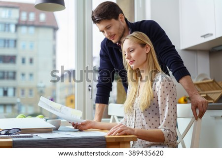 Attractive young European couple looking over papers at table in kitchen next to large window with view of city in background