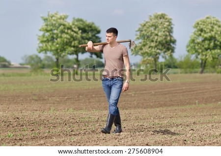 Attractive young farmer with hoe walking in corn field in spring - stock photo