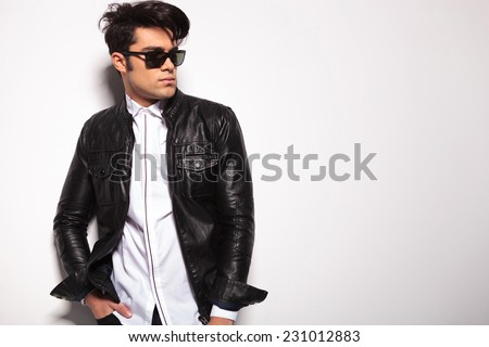 Attractive young fashion man holding his hands in pockets while looking away from the camera.