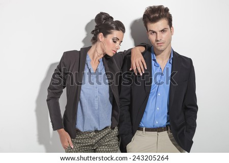 Attractive young fashion man leaning on a wall with his hands in pockets while his girlfriend is looking down and holding her hand on his shoulder. - stock photo