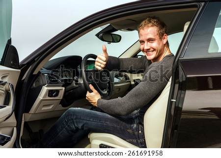 Attractive young fashion man smiling to the camera while showing the thumbs up gesture