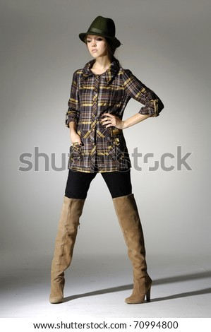 Attractive young fashion model posing in light background
