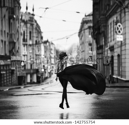 attractive young fashion woman in a city. Grain added. Color it's a author decision - stock photo