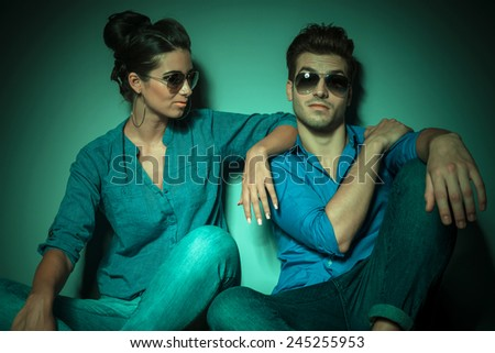 Attractive young fashion woman looking at her lover while he is looking at the camera.