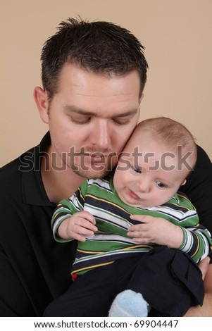 Attractive young father holding his baby boy