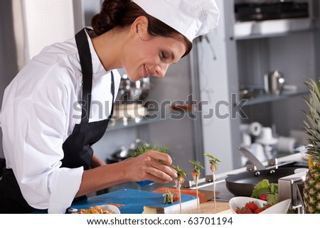 Attractive young female chef adding some garnish to the amuse