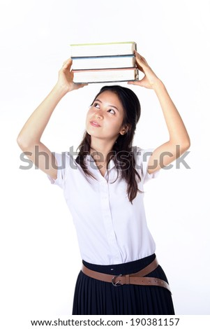 Attractive young female college student carrying a stack of book