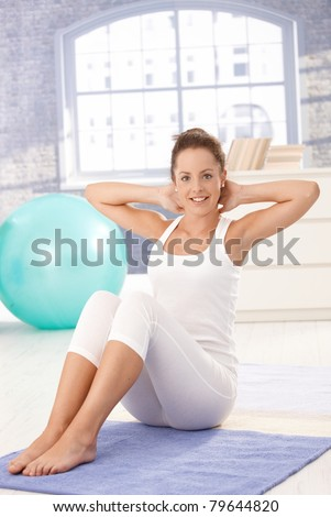 Attractive young female doing exercises on floor at home, smiling.?