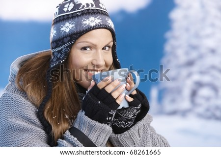 Attractive young female dressed up warm for skiing wearing cap and gloves drinking hot tea smiling front of winter landscape .? - stock photo