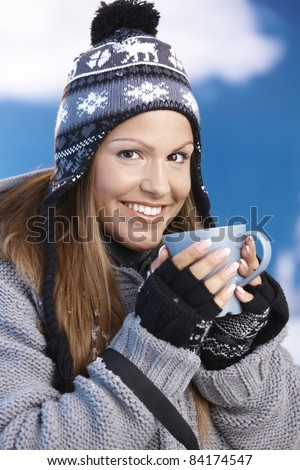 Attractive young female dressed up warm for skiing wearing cap and gloves drinking hot tea smiling front of winter landscape .?