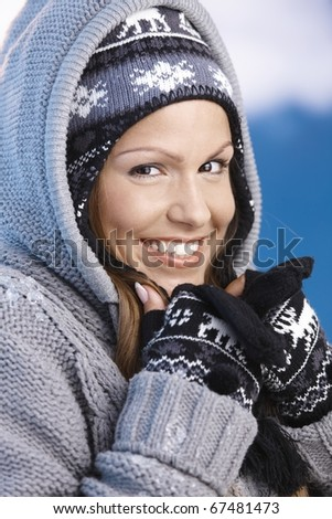 Attractive young female dressed up warm for skiing wearing cap and gloves, resting, smiling. - stock photo