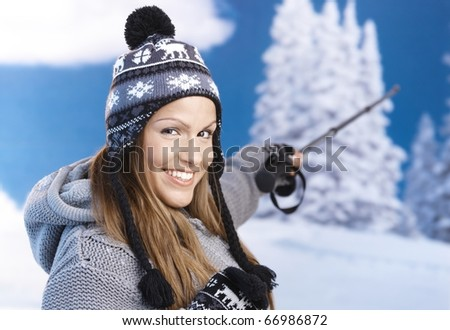 Attractive young female dressed up warm, skiing, pointing to winter landscape, smiling.? - stock photo