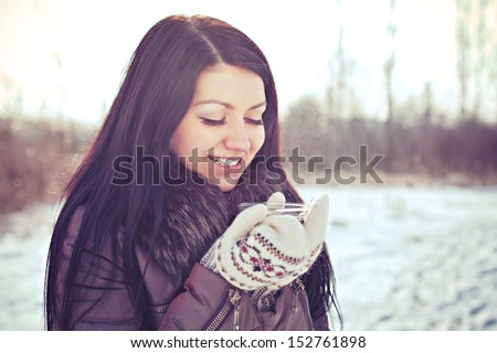 Attractive young female dressed up warm wearing mitten and drinking hot tea