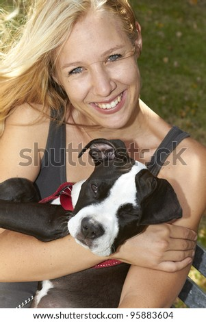 Attractive young female embracing her Pit Bull puppy - stock photo