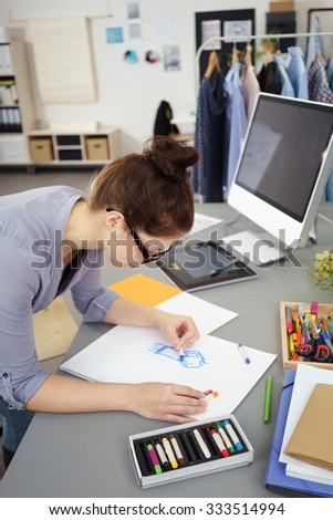 Attractive young female fashion designer working on a new clothing design standing sketching at a table with colored crayons - stock photo