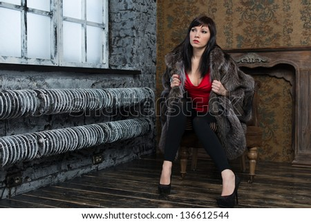 Attractive young female in fur coat sitting near the window, horizontal shot - stock photo