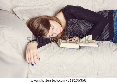 Attractive young female is sleeping on sofa at home with book. - stock photo