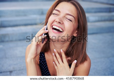 Attractive young female is speaking on the phone and laughing sincerely over grey street stairs background - stock photo