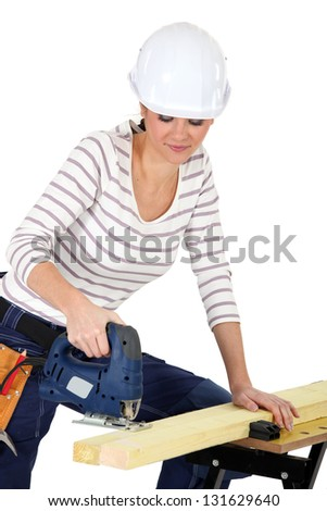 attractive young female joiner using sander machine - stock photo