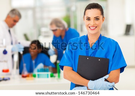 attractive young female lab technician in lab with colleagues - stock photo